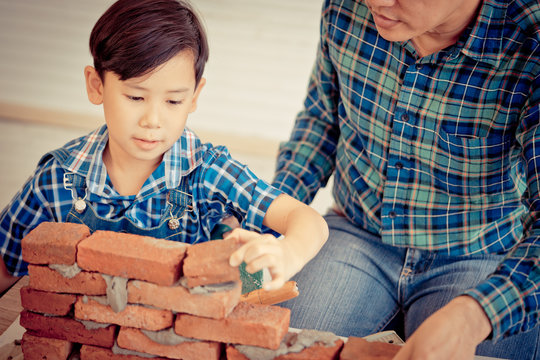 Little boy is learning how to lay down brick work from his builder father in vintage tone