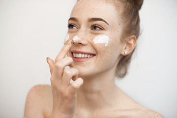 Portrait of a charming young female with red hair and freckles isolated on white applying a anti age cream on her face and nose smiling.