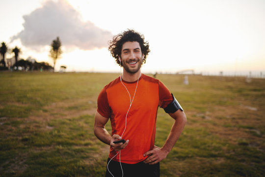 Portrait of a happy fitness young man in earphones holding mobile phone while standing in park looking at camera
