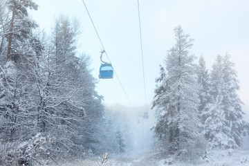 Bansko, Bulgaria winter ski resort with blue gondola lift cabins, forest pine trees and mountains view