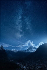 The town of Zermatt and Matterhorn mountain under an epic milky way. Composite image.