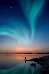 Papiers peints Aurore polaire A man standing by a calm water and looking at the northern lights on the sky with reflections from the water