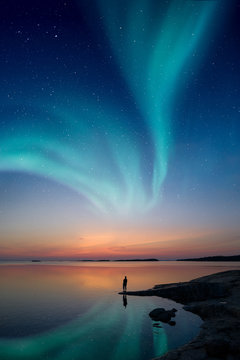 A man standing by a calm water and looking at the northern lights on the sky with reflections from the water