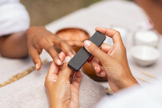 Woman using a buffer to file nail