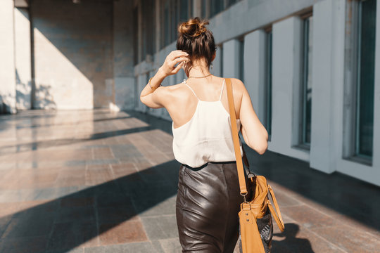 Refined young woman in leather skirt and silk blouse walking confident near a building.
