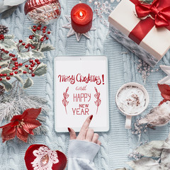Female hand touches tablet computer with Merry Christmas and Happy New Year greeting card on light blue knitted blanket with red Christmas decoration and burning candles. Top view. Flat lay