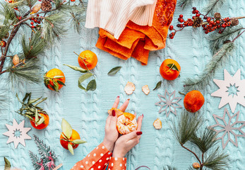 Female hands in orange polka dot blouse pell oranges or tangerines on blue knitted blanket background with warm winter sweaters , fir branches and snowflakes . Top view. Flat lay. Cozy winter mood