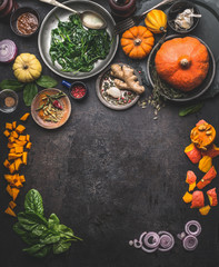 Vegetarian seasonal food background with ingredients for herbs and winter cooking: pumpkin,spinach, ginger, onion. Top view. Frame. Copy space