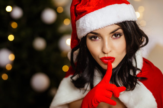 beautiful sexy Snata girl with finger on her red lips showing Shh on the background of the Christmas tree. copy space