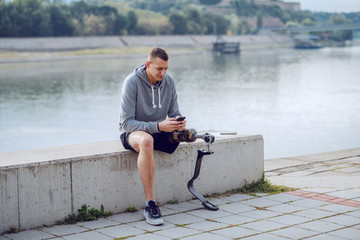 Fotomurales - Handsome fit sporty caucasian handicapped man in sportswear and with artificial leg sitting on quay and typing message on smart phone.