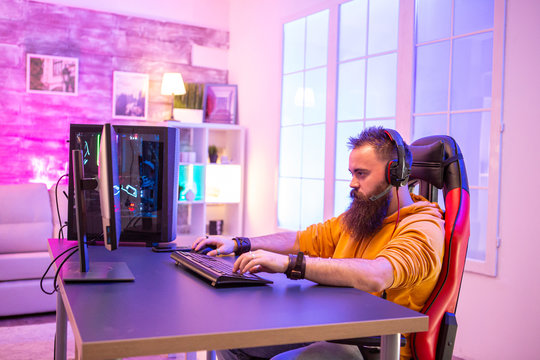 Professional gamer with long beard in front of powerful gaming rig