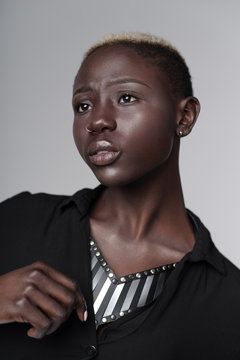 Portrait of beautiful african american woman wearing leather necklace with metal inserts posing on light grey background