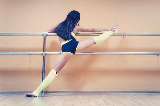 Athletic woman standing near barre in fitness center putting her leg high on the choreographic machine. Brunette dancer in sport outfit warming up before dancing. Stretching in dance class. Work out.
