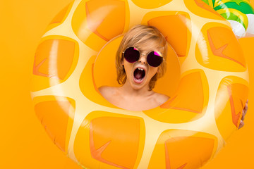 portrait of a fun european blond boy in yellow swimming trunks and sunglasses with a swimming circle pineapple on an orange background