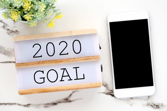 2020 goal on wood box and smart phone with blank screen on white marble background, new year aim to success in business background