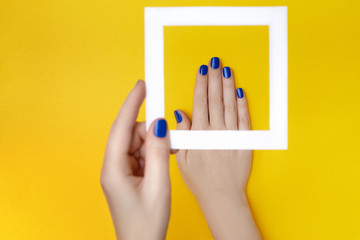 Photo sur Aluminium Manicure Female hands with manicure in trendy classic blue color holding white frame on the yellow background