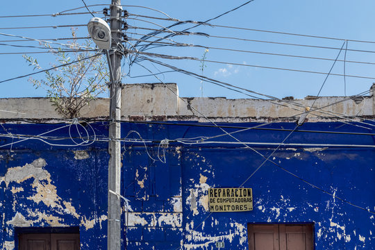 "Bright blue wall of a repair shop in the small town of Comitan de Doinguez, the yellow plaque reads ""Monitors and computer repairs""."