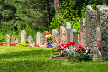 Curved row of grave stones with red and pink flowers Fototapete