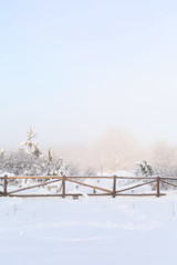 Christmas or New Year winter panorama with snow forest pine trees, fog and wooden fence