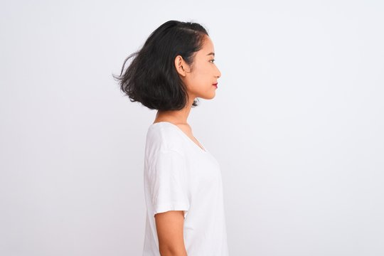 Young chinese woman wearing casual t-shirt standing over isolated white background looking to side, relax profile pose with natural face with confident smile.