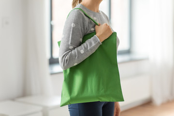 consumerism and eco friendly concept - woman with green reusable canvas bag for food shopping on grey background