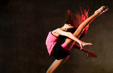 Young slim athletic girl gymnast dancer jumping up stretching doing gymnastic exercises in studio on dark wall