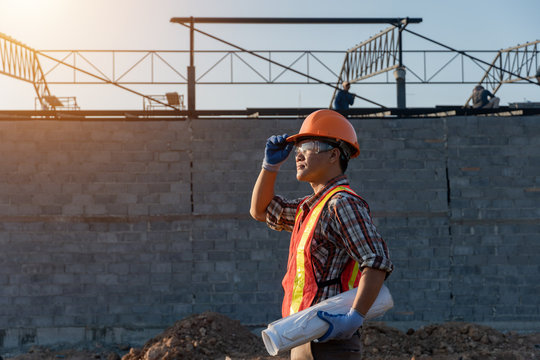 Engineer Asia smart handsome and holding the digital blueprint in constructions site