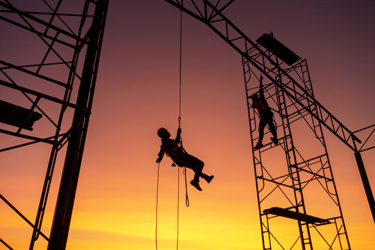 Male working abseiling on a construction site silhouette worker