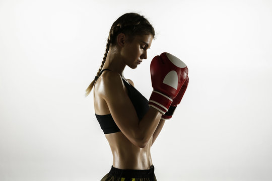 Fit caucasian woman in sportswear boxing isolated on white studio background. Novice female caucasian boxer preparing for working out and training. Sport, healthy lifestyle, movement concept.