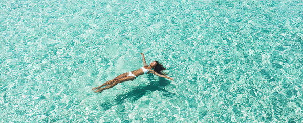 Obraz Woman in white bikini lying on transparent turquoise water surface on beach. Travel and vacations concept. Tropical background with empty space - fototapety do salonu