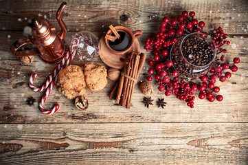 Black coffee with cookies cinnamon and spice on old wooden board in rustic style, top view. Christmas composition with baking and hot drink in cup.