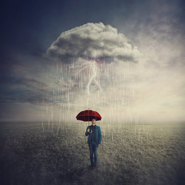 Surreal scene as man stands outdoors under umbrella due a single mysterious storm cloud raining only over him. Find solution to escape crisis situations. Business security and protection concept.