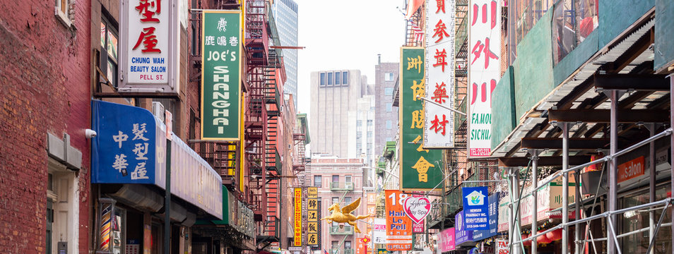 Chinese business signs on brick facades in Chinatown's Pell Street, New York City. Taken on September the 26th, 2019