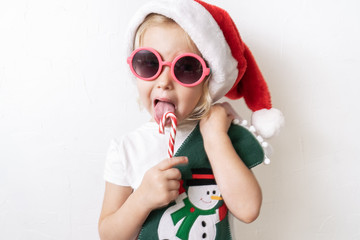 Christmas: A little girl in a red santa cap a striped lollipop in his hands.