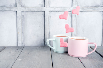 Two pastel cups with hot cocoa drink or latte coffee with flying red and pink hearts levitation marshmallows. Valentine's day greetings background. Love winter holidays cute picture.