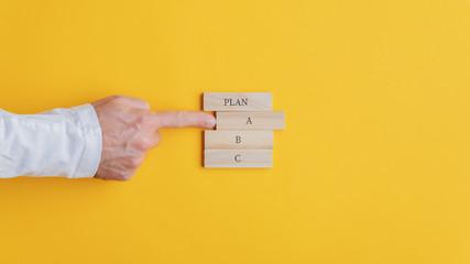 Hand of a businessman choosing a plan A option
