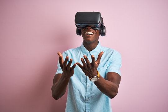 Young african american man playing virtual reality game using goggles