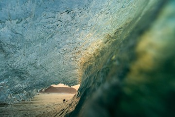 Detailed picture of a sea wave during sunset with mountains on the background in Portugal