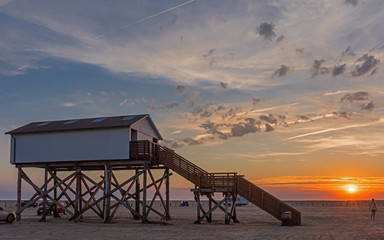 Stilt houses on the beach of St. Peter-Ording at sunset; Germany
