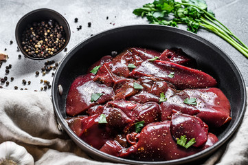 Raw duck liver in a frying pan. Gray background. Top view