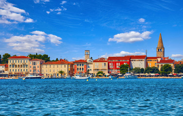 Porec, Croatia. Antique tower in old town. Istria peninsula in Adriatic Sea. View from water at old Mediterranean architecture buildings. Coastline and tower of Church.