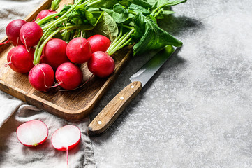 Fototapeta Fresh red radishes in a wooden bowl. Farm organic vegetables. Gray background. Top view. Space for text obraz
