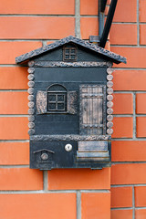 Vintage metallic bronze mailbox in shape of little house with window and door hanging on the brick wall