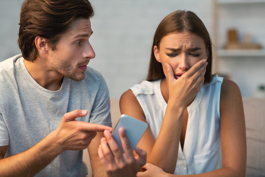 Jealous Boyfriend Showing Phone To Girlfriend Sitting On Couch Indoor