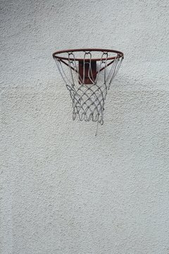 Vertical picture of a red basketball hoop on a dirty white wall during daytime