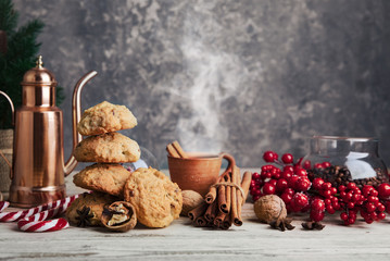 Christmas treat with hot coffee cookies and candies. Festive card new year decoration on wooden board in rustic style.