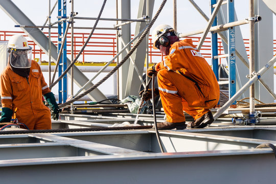 Offshore fitters preparing acetylene hoses for cutting tie-down od a structure prior to heavy lift
