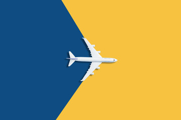Flat lay design of travel concept with plane on blue and yellow background with copy space Fototapete