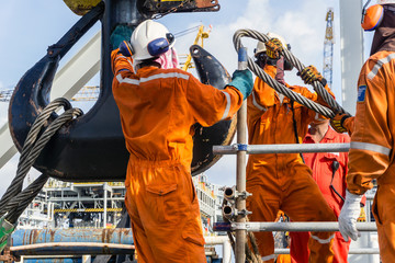 Offshore workers installing a heavy lifting sling onto a crane hook on board a construction work barge at oil field