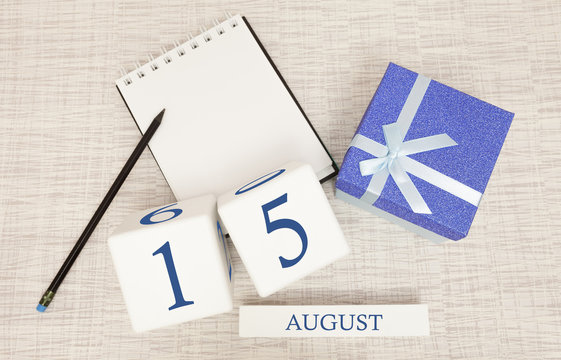 Calendar with trendy blue text and numbers for August 15 and a gift in a box.